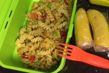 Studený těstovinový salát s malými kousky drůbežiho masa a zeleninou, banán